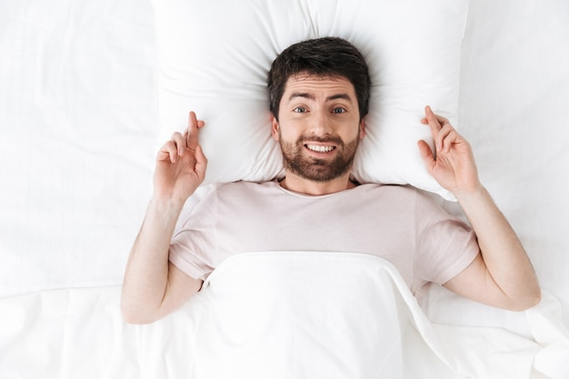 Счастливый молодой человек утром под одеялом в постели делает обнадеживающий жест