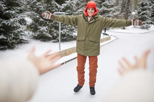 Счастливый молодой человек в теплой одежде катается на коньках на катке зимой в парке