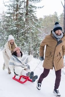 公園での遊び中に別の女性が後ろを走っている間、陽気な女の子とそりを引っ張る冬服の幸せな若い男