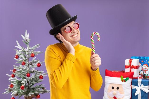 Счастливый молодой человек в желтой водолазке и очках в черной шляпе держит конфету, весело улыбаясь, стоя рядом с елкой и подарками на фиолетовом фоне