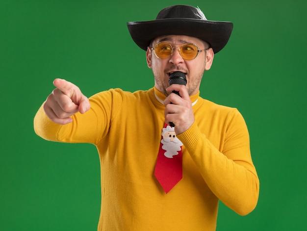 緑の壁の上に立っている側にインデックスfignerでマイクを指している面白い赤いネクタイと黄色のタートルネックとメガネで幸せな若い男