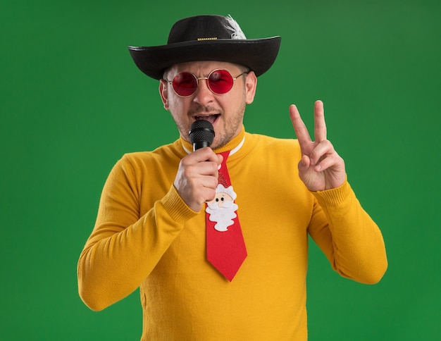 緑の壁の上に立っているvサインを示すマイクの歌を保持している面白い赤いネクタイと黄色のタートルネックとメガネで幸せな若い男