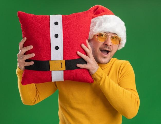 노란색 터틀넥과 산타 모자에 행복 한 젊은 남자가 카메라를보고 빨간색 재미 베개를 들고 안경을 쓰고 녹색 배경 위에 서 놀란