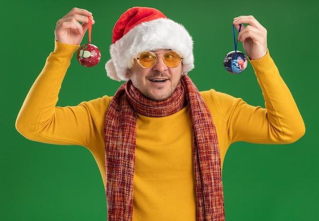 Счастливый молодой человек в желтой водолазке и шляпе санта-клауса в очках держит игрушки для елки, глядя в камеру, весело улыбаясь, стоя на зеленом фоне