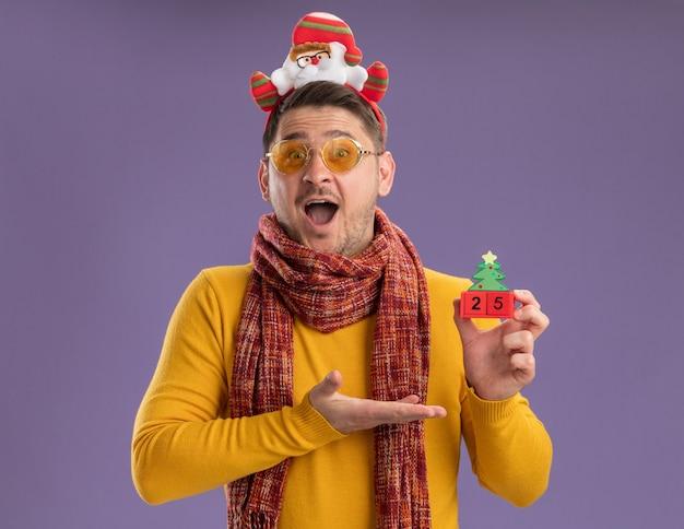 Счастливый молодой человек в желтой водолазке с теплым шарфом и очках в забавной оправе с дедом морозом на голове представляет игрушечные кубики с номером двадцать пять, стоящие над фиолетовой стеной