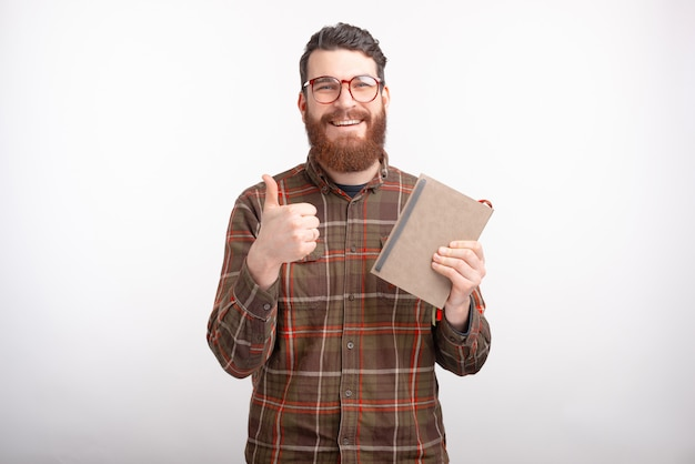 Happy young man is holding a notebook or a book, smiling at the camera, showing like button or thumb up on white space.