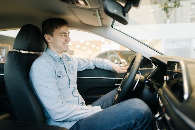 행복한 청년이 자동차 대리점에서 새 차의 바퀴 뒤에 앉아 있다