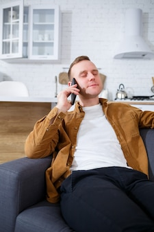 幸せな若い男は、コーヒーを飲みながらリビングルームのソファに座って、電話で話している。