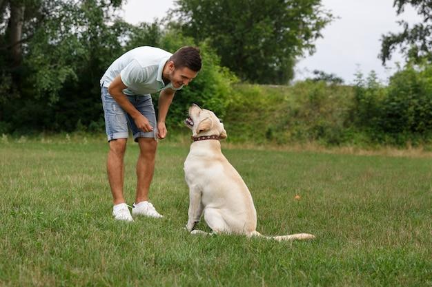 幸せな若い男は屋外犬ラブラドールを訓練します。