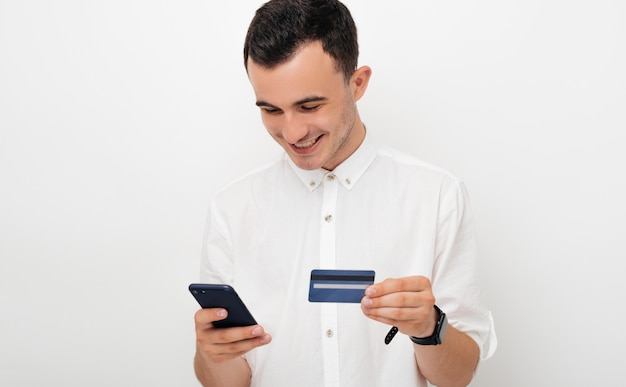 幸せな若い男はモバイルバンキングを使用しているか、白い背景の上何かをオンラインで購入します。