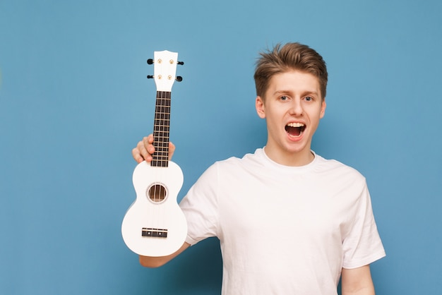 Happy young man isolated on blue with ukulele in hand