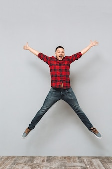 Happy young man jumping over grey wall.