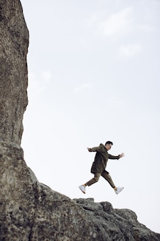 Счастливый молодой человек прыгает из скалы. концепция успеха