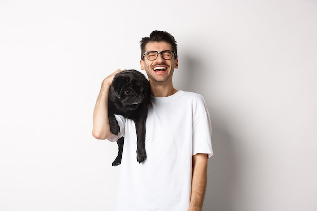 Happy young man laughing carefree, holding cute black dog, pug breed, on shoulder and having fun, standing over white.