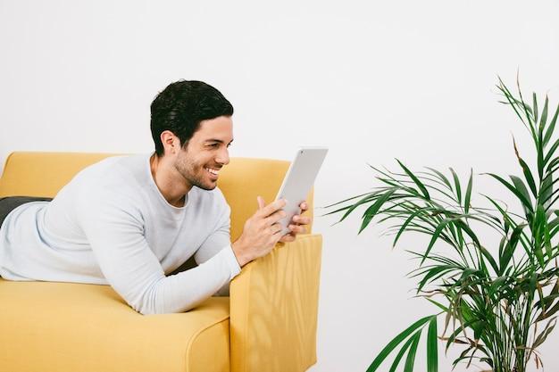 幸せな若い男は、タブレットでソファに横たわる