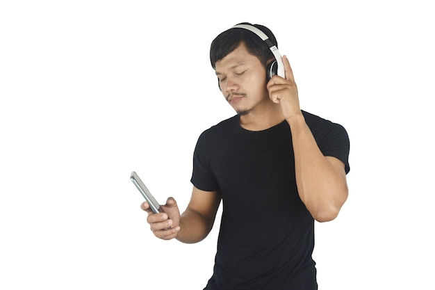 Happy young man listening to music with headphones on white background copy space