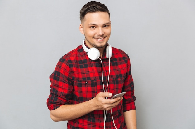 Happy young man listening music with headphones.