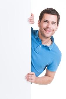 Il giovane felice osserva fuori dall'insegna in bianco - isolato su bianco.