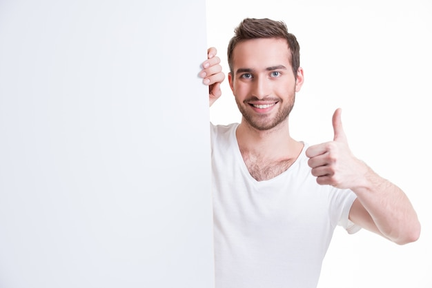 Happy young man look out from blank banner with thumb up - isolated on white