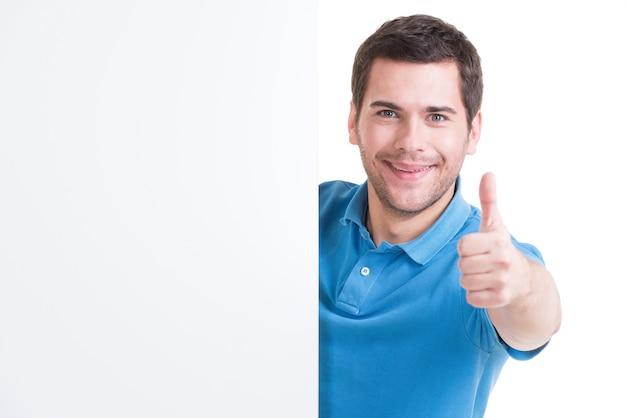 Il giovane felice osserva fuori dall'insegna in bianco con il pollice in su - isolato su bianco.
