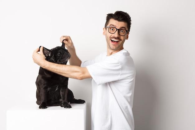 カメラを見て、かわいい犬の耳を見せて、喜びを感じて、ペットを採用し、白い背景の上に立って幸せな若い男