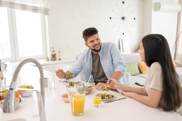 테이블 옆에서 직접 만든 야채 샐러드와 오렌지 주스를 먹으면서 대화하는 동안 웃는 얼굴로 아내를 바라보는 행복한 청년