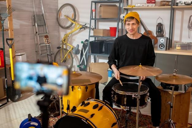 그의 차고에서 온라인 관객을 위해 드럼 음악의 비디오 레슨을 녹음하는 동안 스마트 폰 카메라를보고 행복 한 젊은 남자