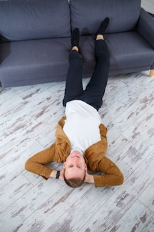 Happy young man lying on the floor near the sofa in the living room and resting