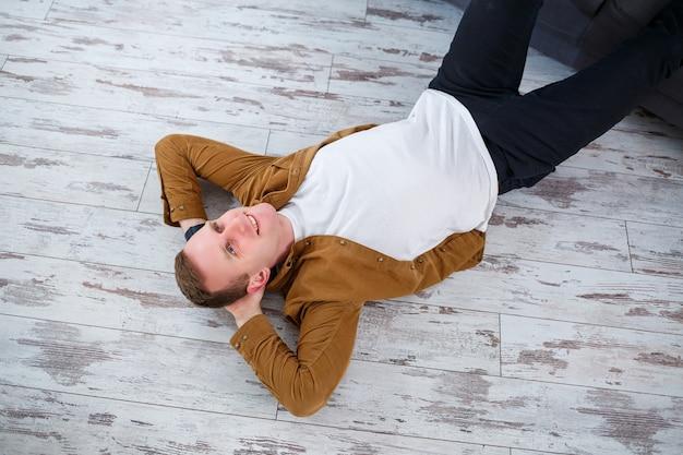 거실 소파 근처 바닥에 누워 쉬고 있는 행복한 청년