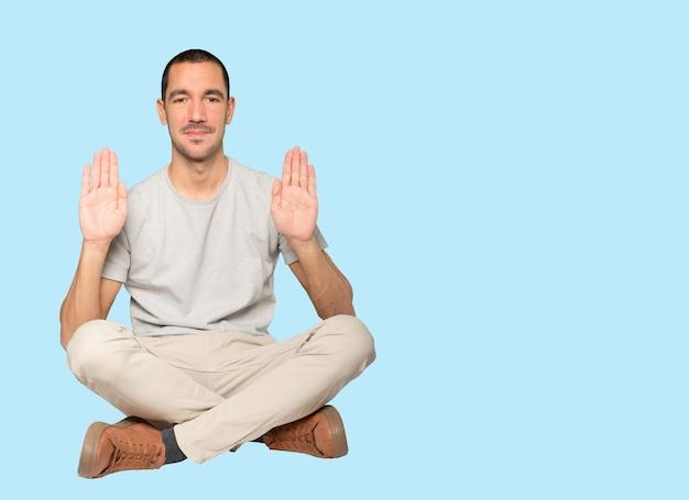 Счастливый молодой человек делает жест стоп ладонью