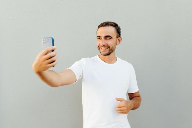회색 벽에 고립 된 selfie를 만드는 행복 한 젊은 사람
