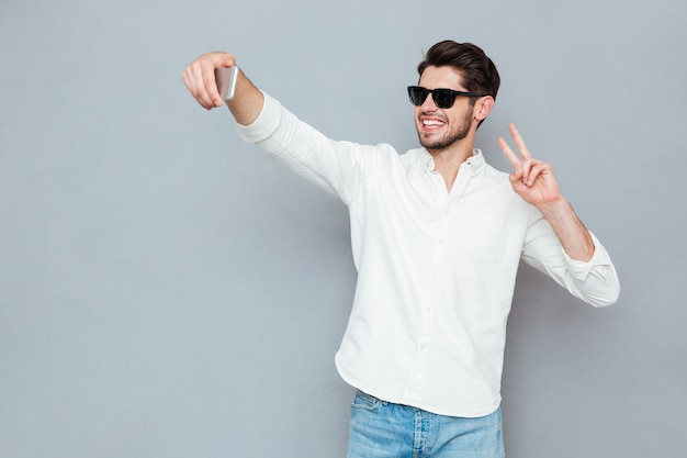 Happy young man making selfie photo on smartphone over gray background