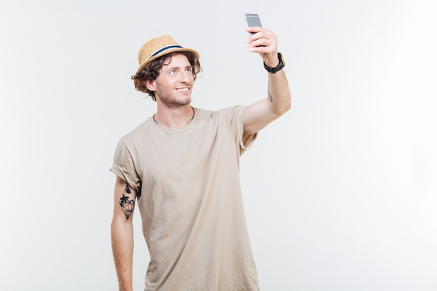 Happy young man making selfie photo on smartphone over white background
