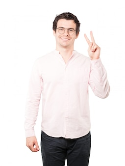 Happy young man making a victory gesture with his fingers