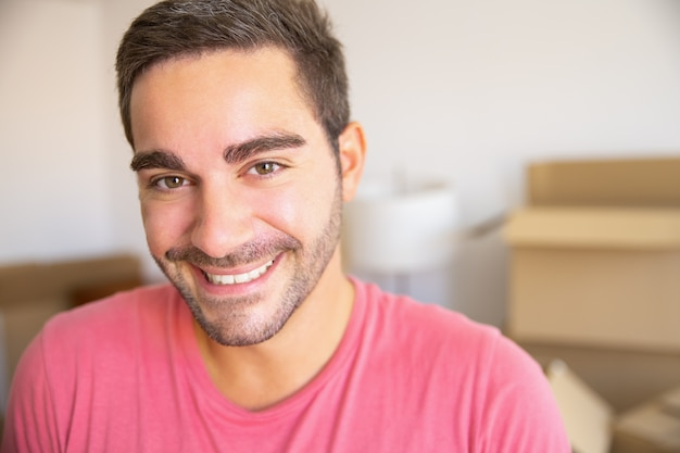 Happy young man moving in new apartment, standing in front heap of opened carton boxes, looking at camera