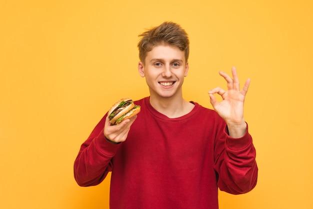 Счастливый молодой человек на желтом с гамбургером в руке показывает пальцами знак ок