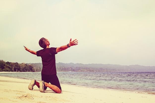 손을 상승 열 대 하얀 모래 열 대 해변에서 행복 한 젊은 남자. 남자는 하늘에 그의 손으로 무릎을 꿇고. 태양, 여행, 휴가, 물, 활동,