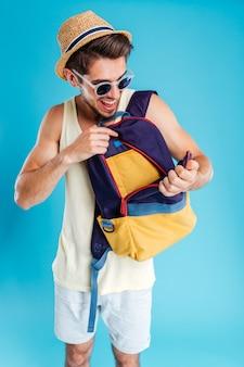 Счастливый молодой человек, открывая сумку