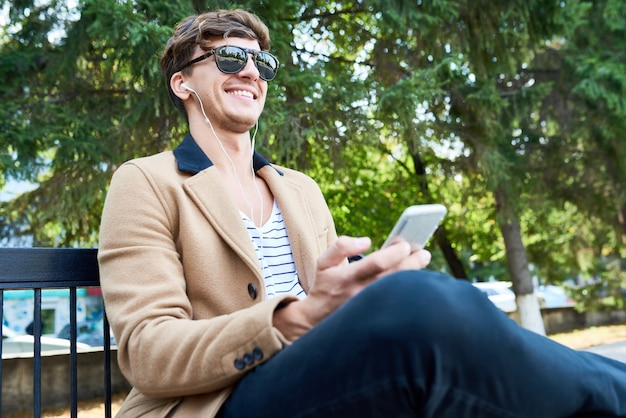 Happy young man in park using smartphone