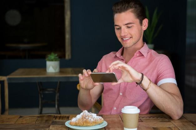 Счастливый молодой человек фотографирует еду на столе в кафе