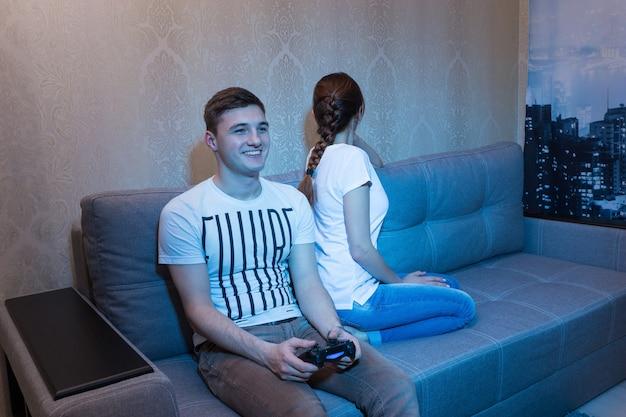 집에 있는 소파에 앉아 기쁨의 환한 미소를 지으며 콘솔을 들고 비디오 게임을 하는 행복한 젊은 남자가 관심 부족으로 인해 여자친구가 등을 돌리고 기분이 상했다