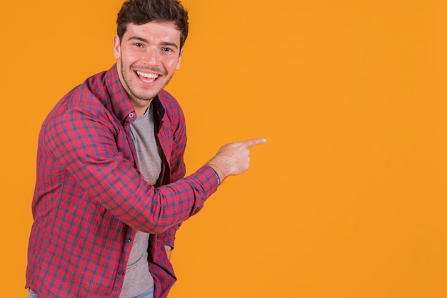 Happy young man pointing his finger on an orange background