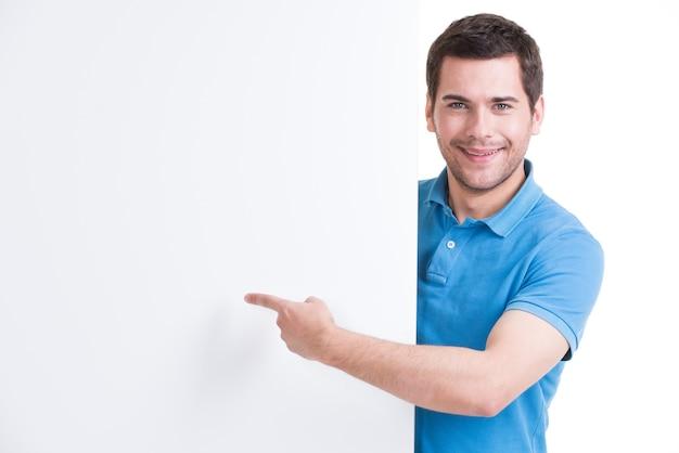 Il giovane felice indica il dito su un'insegna in bianco - isolata su bianco.
