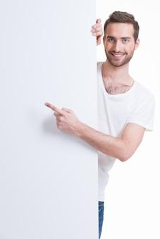 幸せな若い男は空白のバナーに指を指す-白で隔離