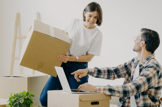 Happy young man points into laptop computer, searches new design for flat, busy woman carries boxes