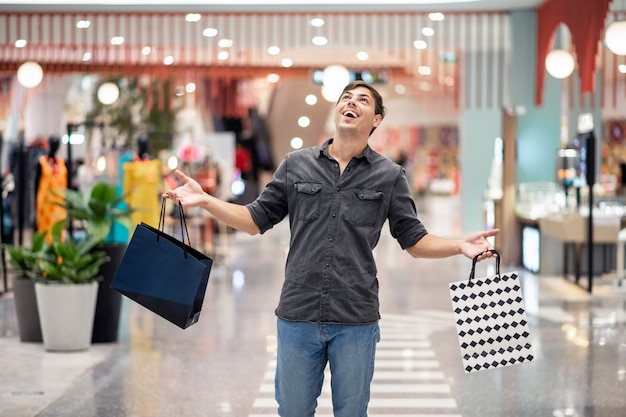 Happy young man posing holding small packages from the store in raised hands, expressing emotion