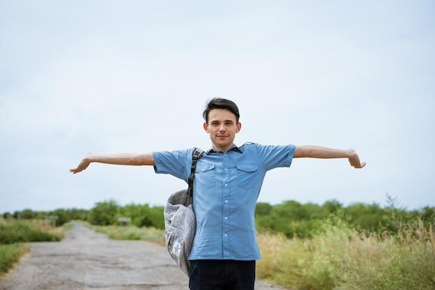 제기 팔으로 포즈를 취하는 행복 한 젊은 남자, 도로에 서서 거리를 찾고