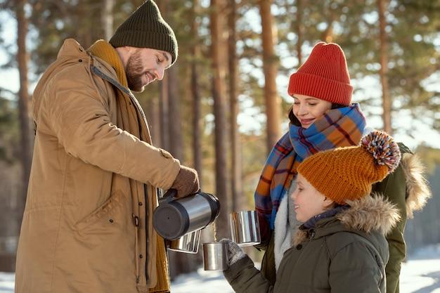 松の木に対してカメラの前に立っている間彼の妻と娘の金属製マグカップに熱いお茶を注ぐ幸せな若い男