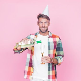 Happy young man pouring wine into glass on pink background