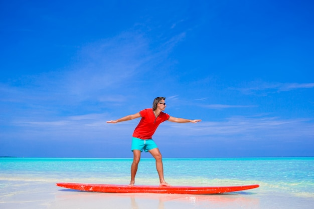 Happy young man practicing surfing position on surfboard